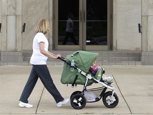 Woman-pushes-child-stroller