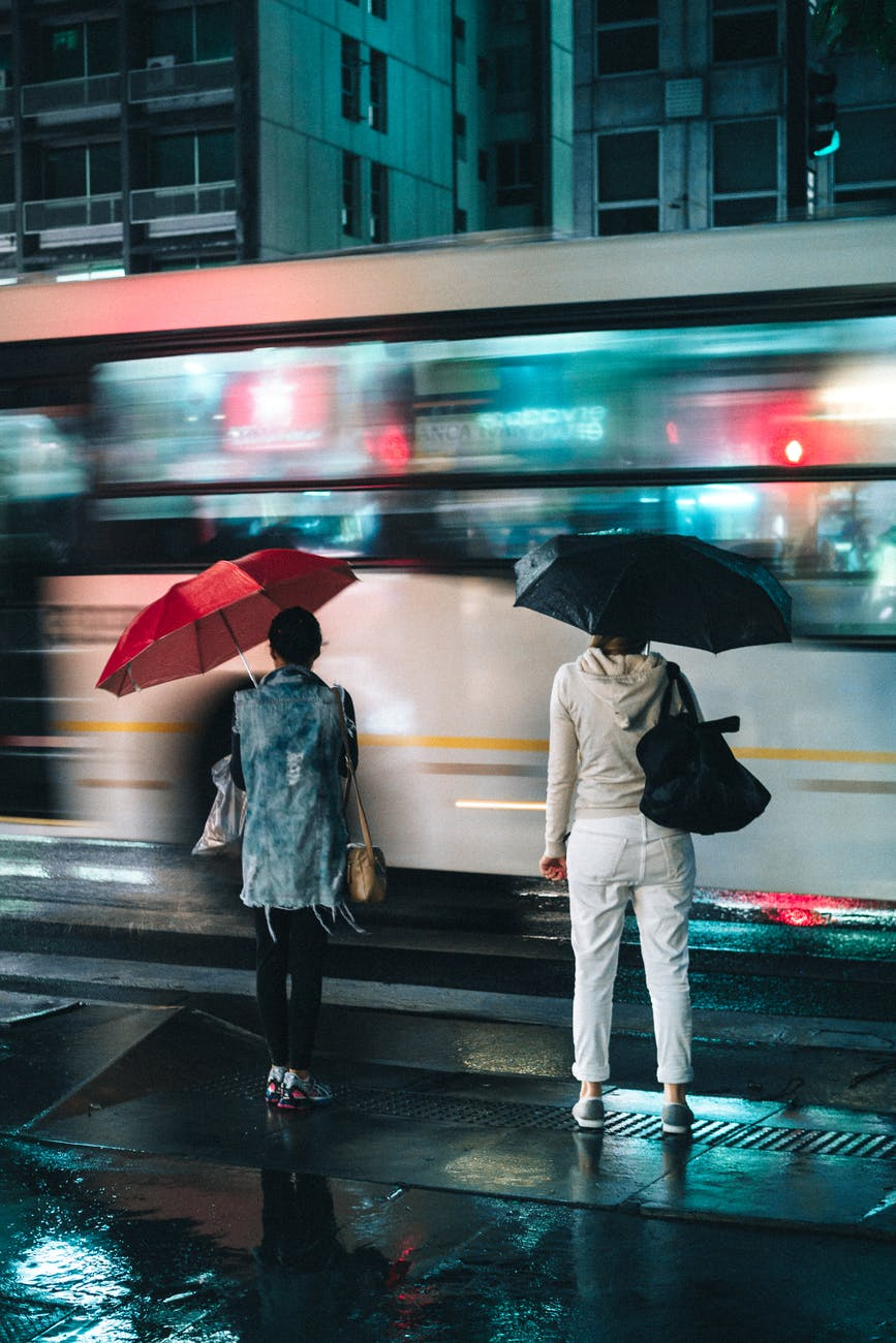 women standing under open umbrellas outdoors during nighttime