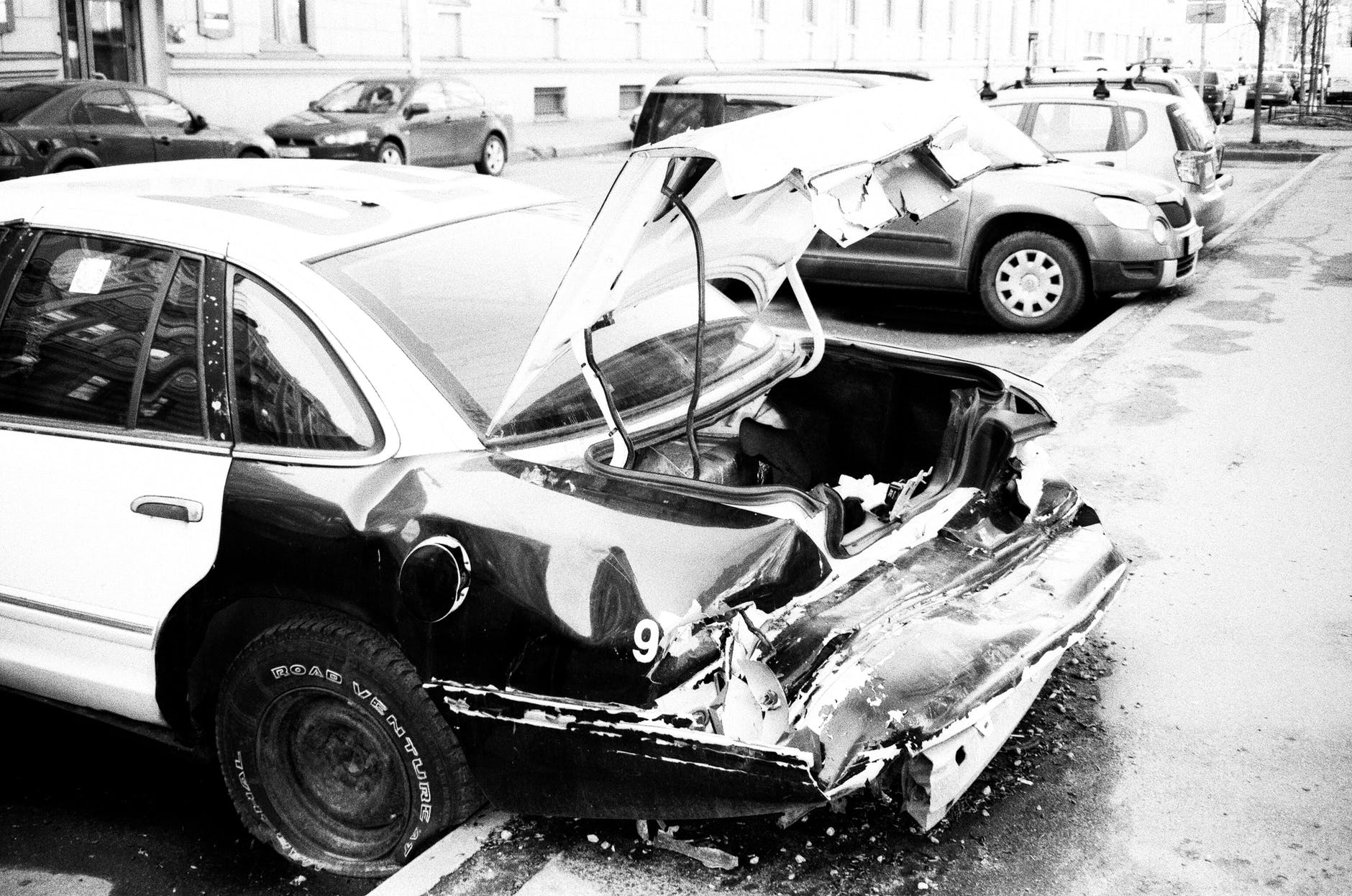 grayscale photo of wrecked car parked outside